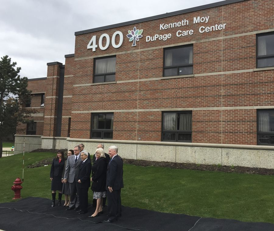 Kenneth Moy poses with some DuPage County Board members and state lawmakers Tuesday after a new sign was unveiled on the Kenneth Moy DuPage Care Center in Wheaton.
