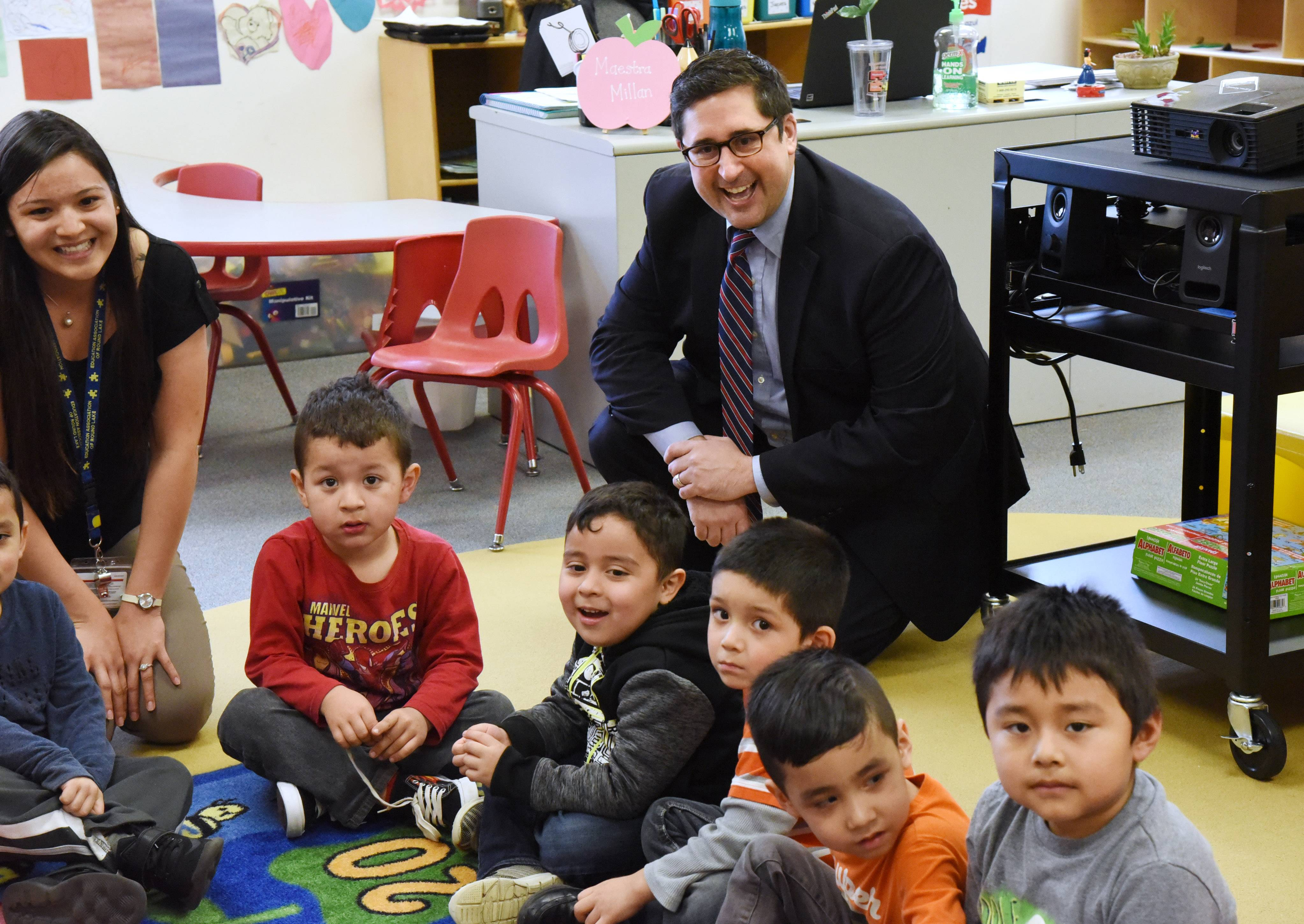 State Rep. Sam Yingling, a Grayslake Democrat, visits a bilingual class taught by Yuri Millan, left, during a stop at the Round Lake Early Education Center on Tuesday.