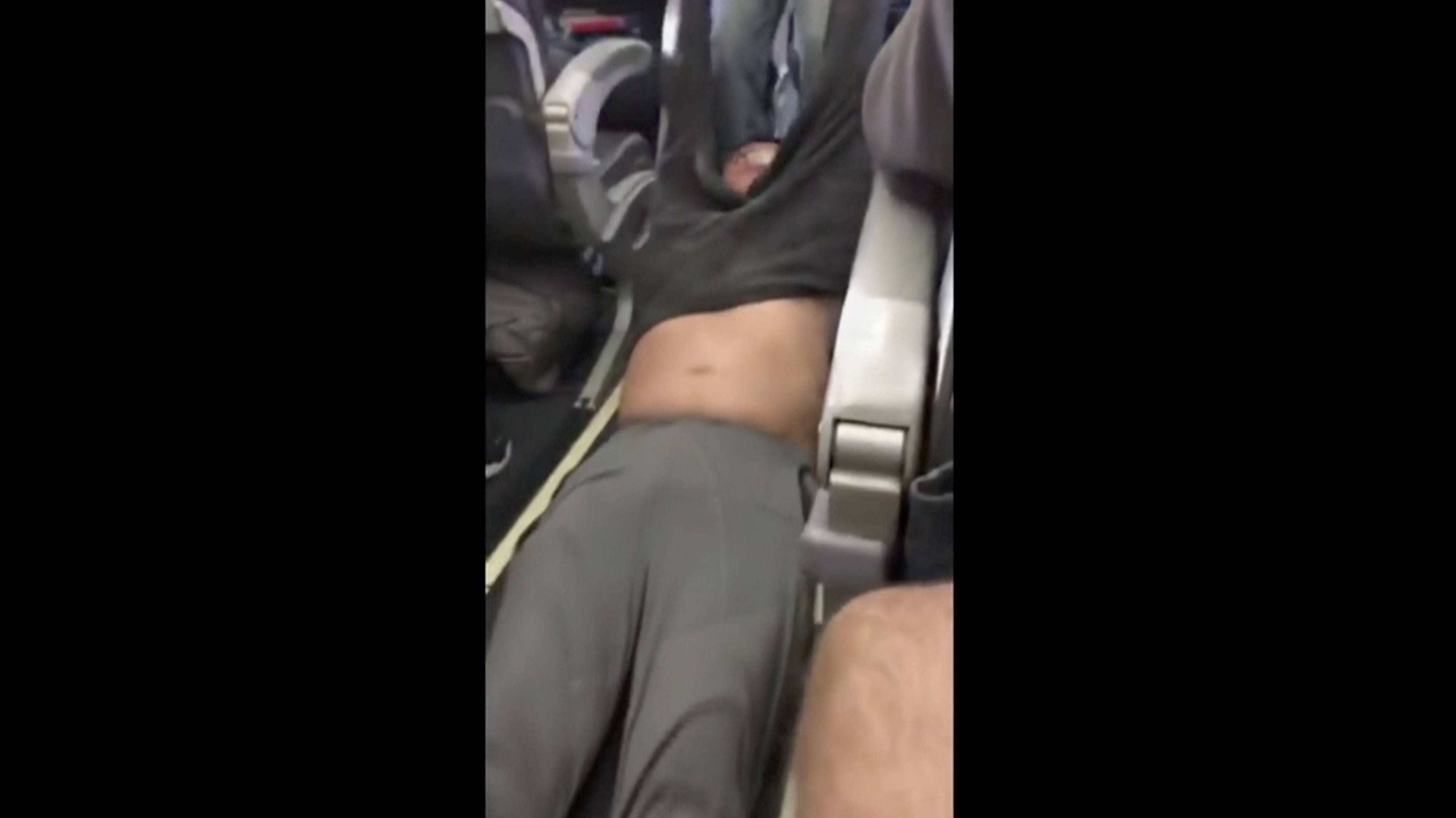 This image made from a video provided by a passenger shows another passenger being removed Sunday from a United Airlines flight in Chicago.