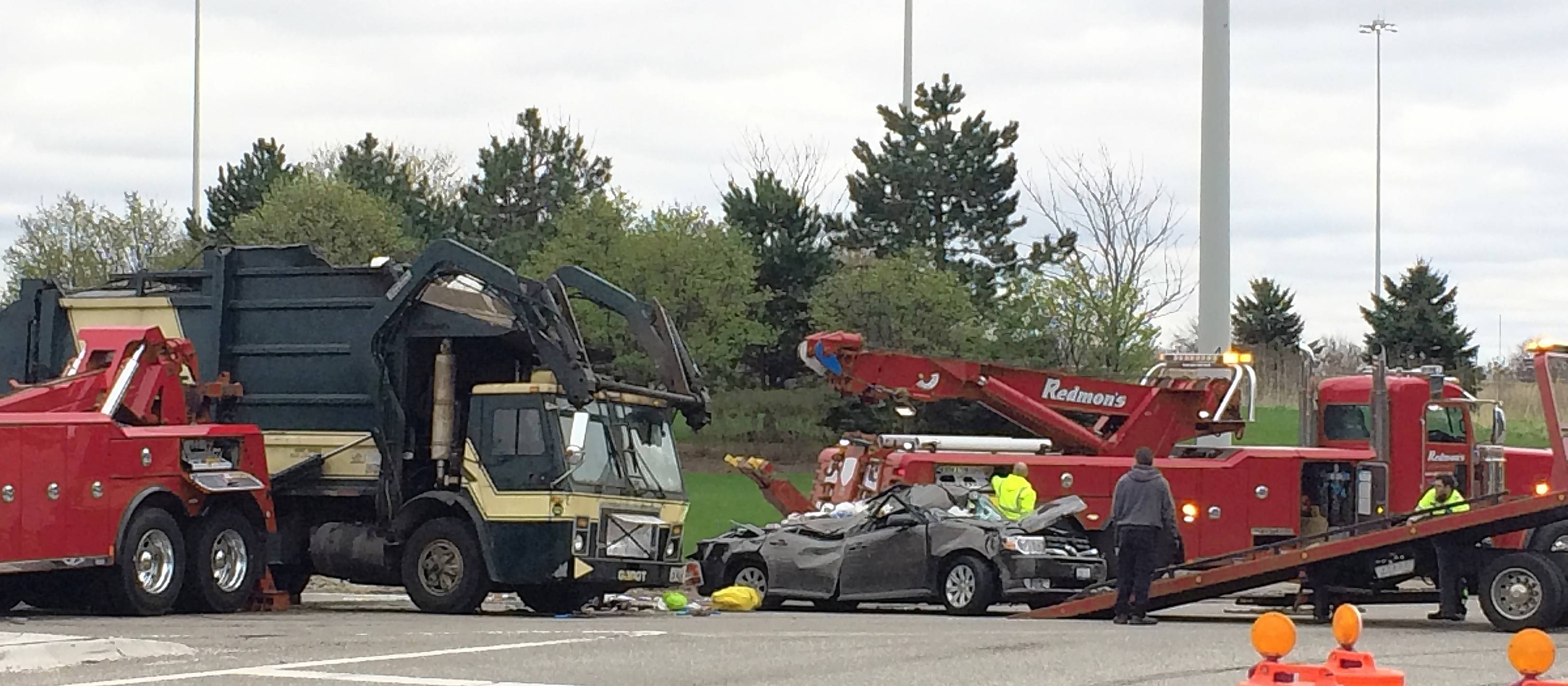 Crews clean up the wreckage near the southbound ramp of Route 53 on Higgins Road in Schaumburg after a garbage truck tipped over onto a car Tuesday.