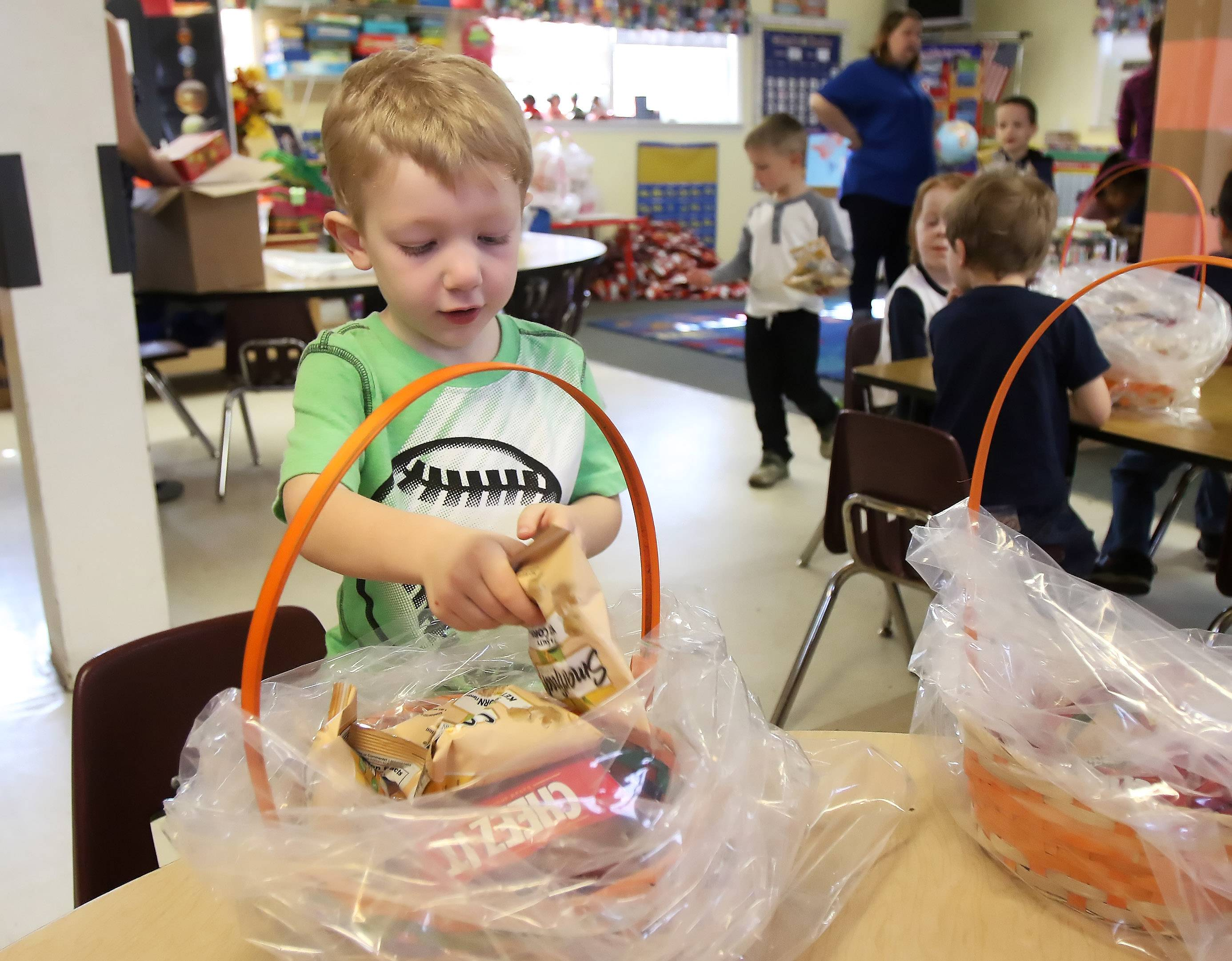 Preschooler Landon Bunkelman, 4, of Lake Villa fills an Easter basket Wednesday at the Lindenhurst Early Childhood Center. More than 400 baskets will be given to local charities and hospitals for kids who are battling illness or in need.