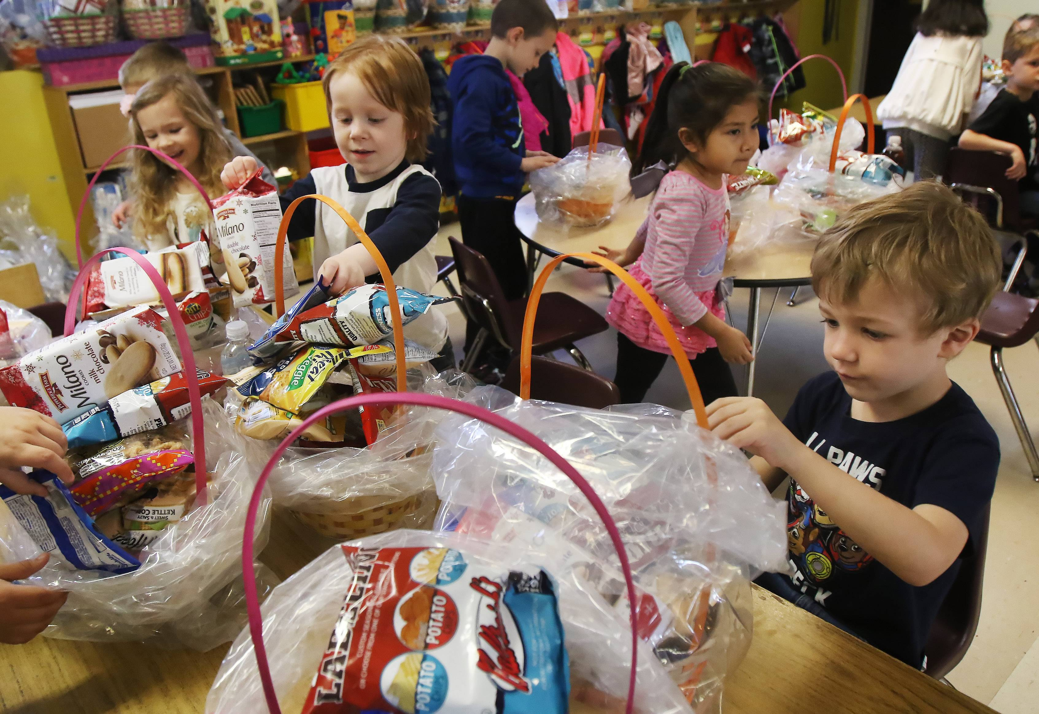 Preschoolers Liam Holland, 4, of Grayslake, right, and Radley Schackmuth, 4, of Lake Villa join classmates as they make Easter baskets Wednesday at the Lindenhurst Early Childhood Center.