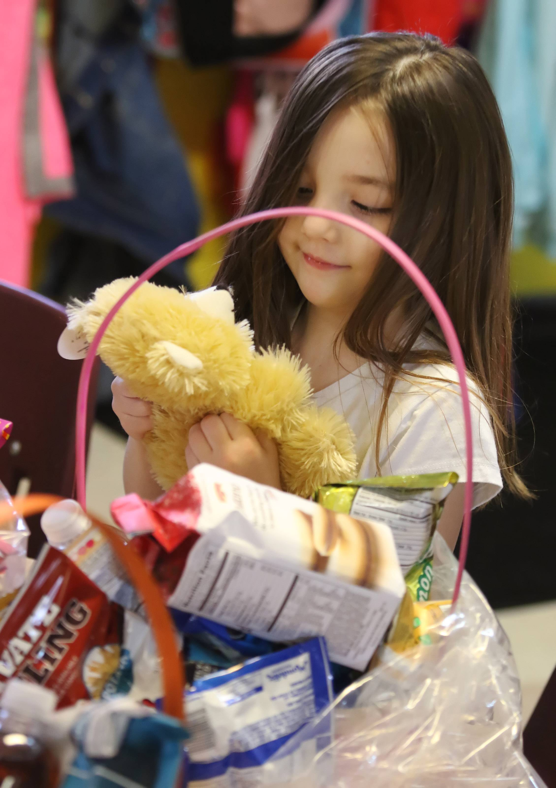 Preschooler Trinity Paice, 5, of Lake Villa hugs a teddy bear before placing it in an Easter basket Wednesday at the Lindenhurst Early Childhood Center.