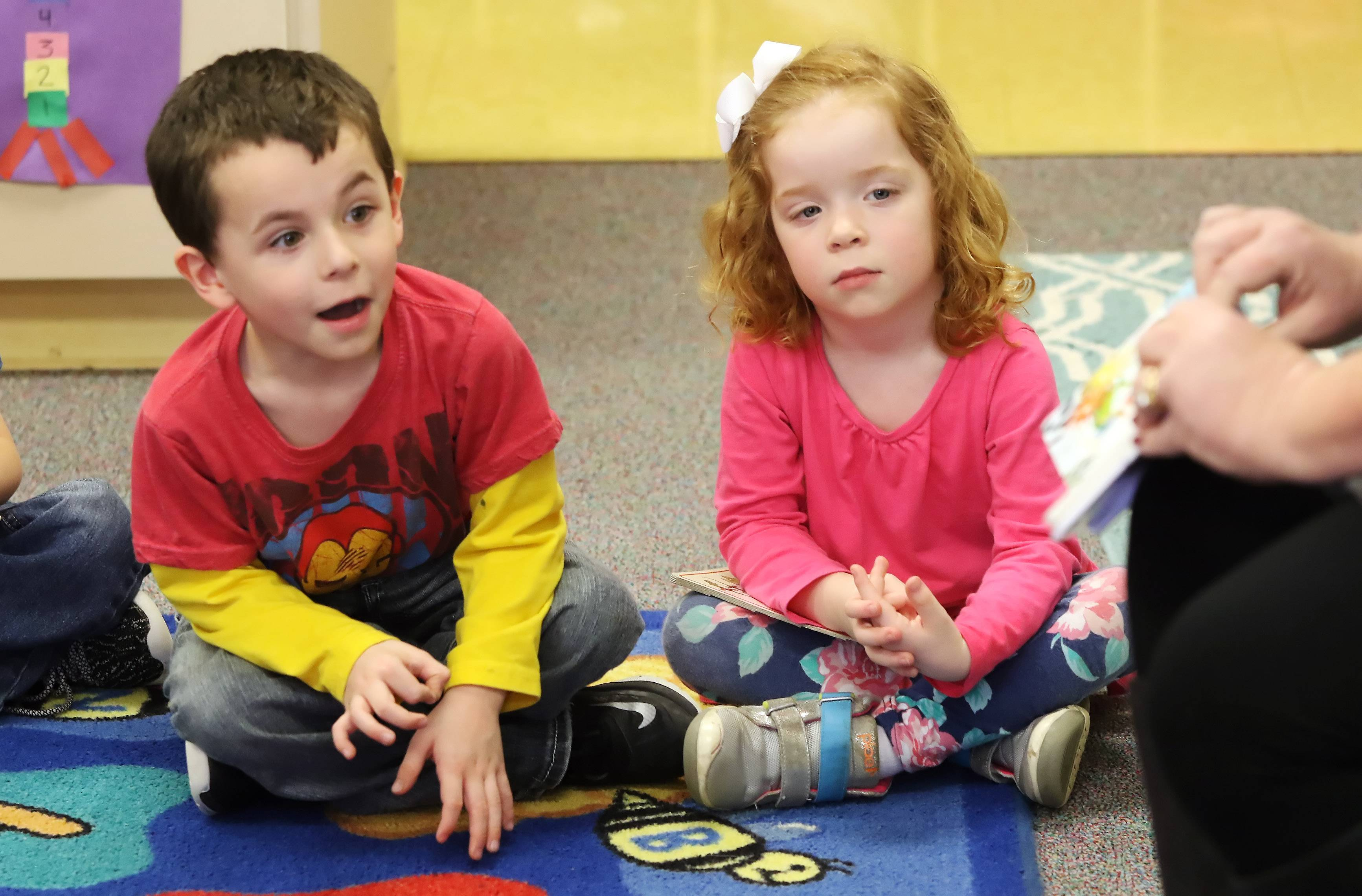 "Preschoolers Declan Clemons, left, and Lacy Christoffers listen Tuesday as Ginny O'Connell, creative director at Cottage Door Press, reads ""Jack and the Beanstalk"" at the Round Lake Early Childhood Center. More than 50 books were donated to the center by Cottage Door Press."