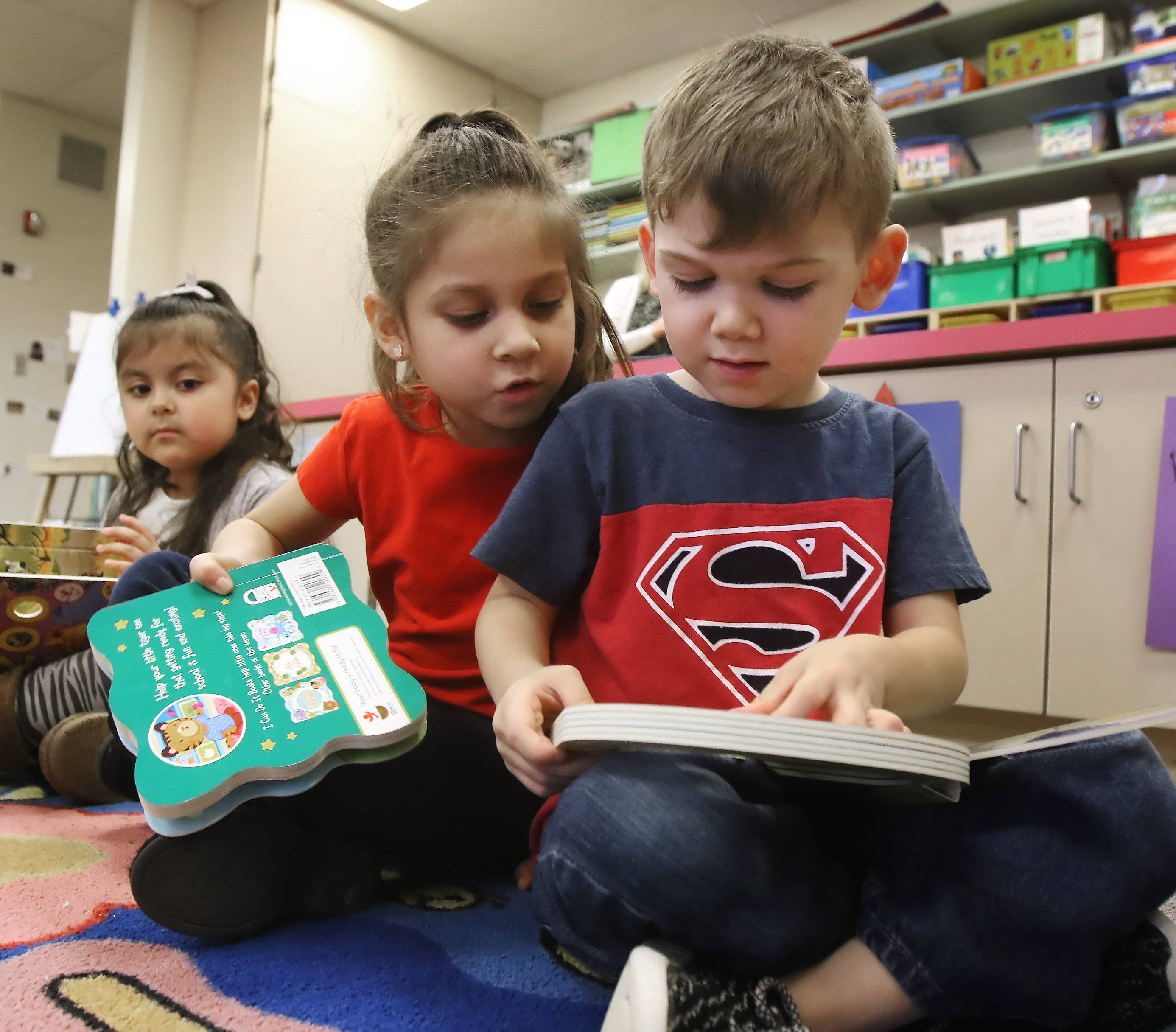 Preschoolers Mia Teo, left, and Eragon Ferreyra read new books Tuesday at the Round Lake Early Childhood Center. More than 50 books were donated to the center after teacher Kalie Skiles penned a guest column in the Daily Herald about the school's funding struggles.