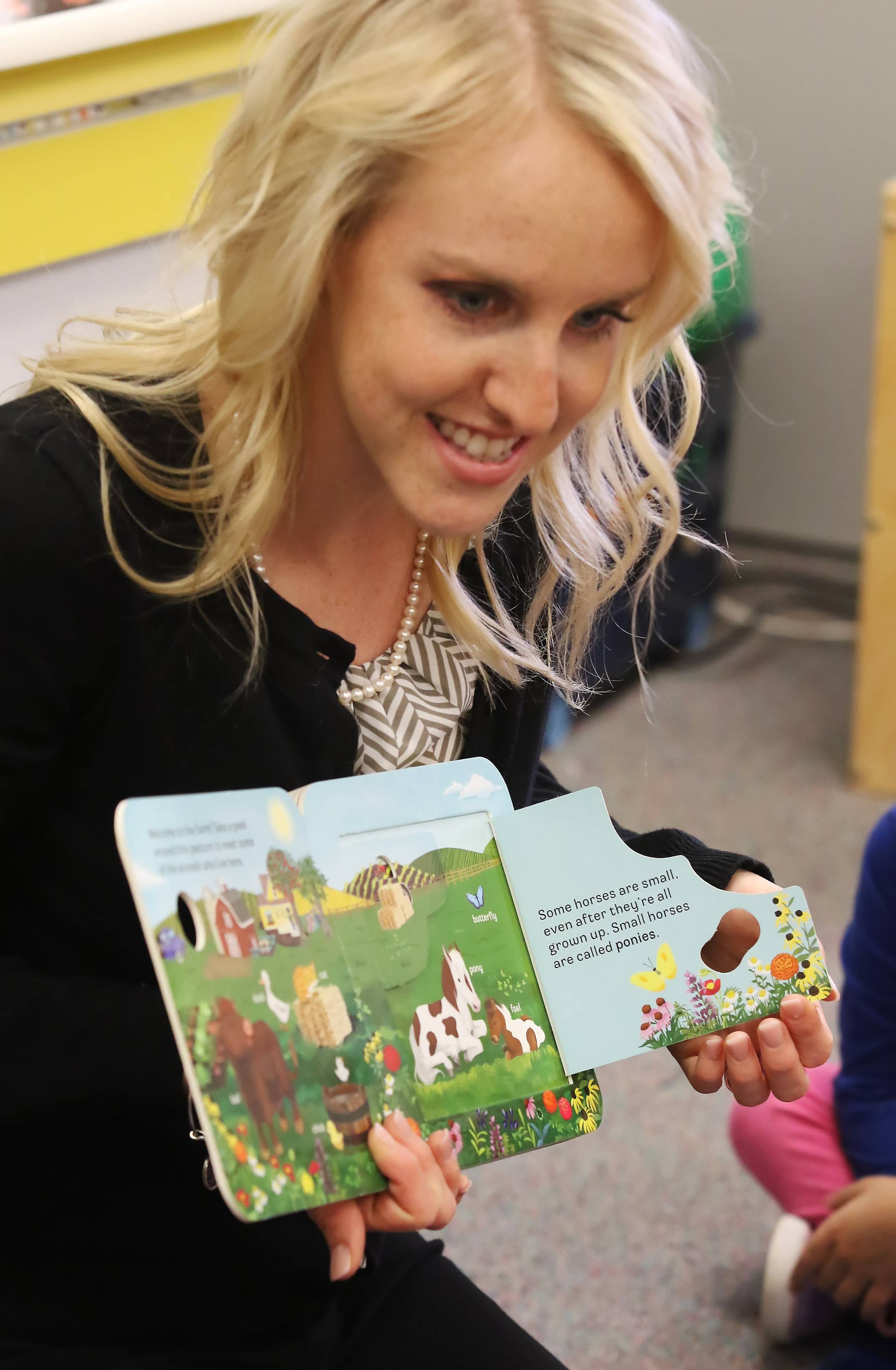 "Preschool teacher Kali Skiles reads ""Peek-A-Flap Moo"" to her students Tuesday at the Round Lake Early Childhood Center."