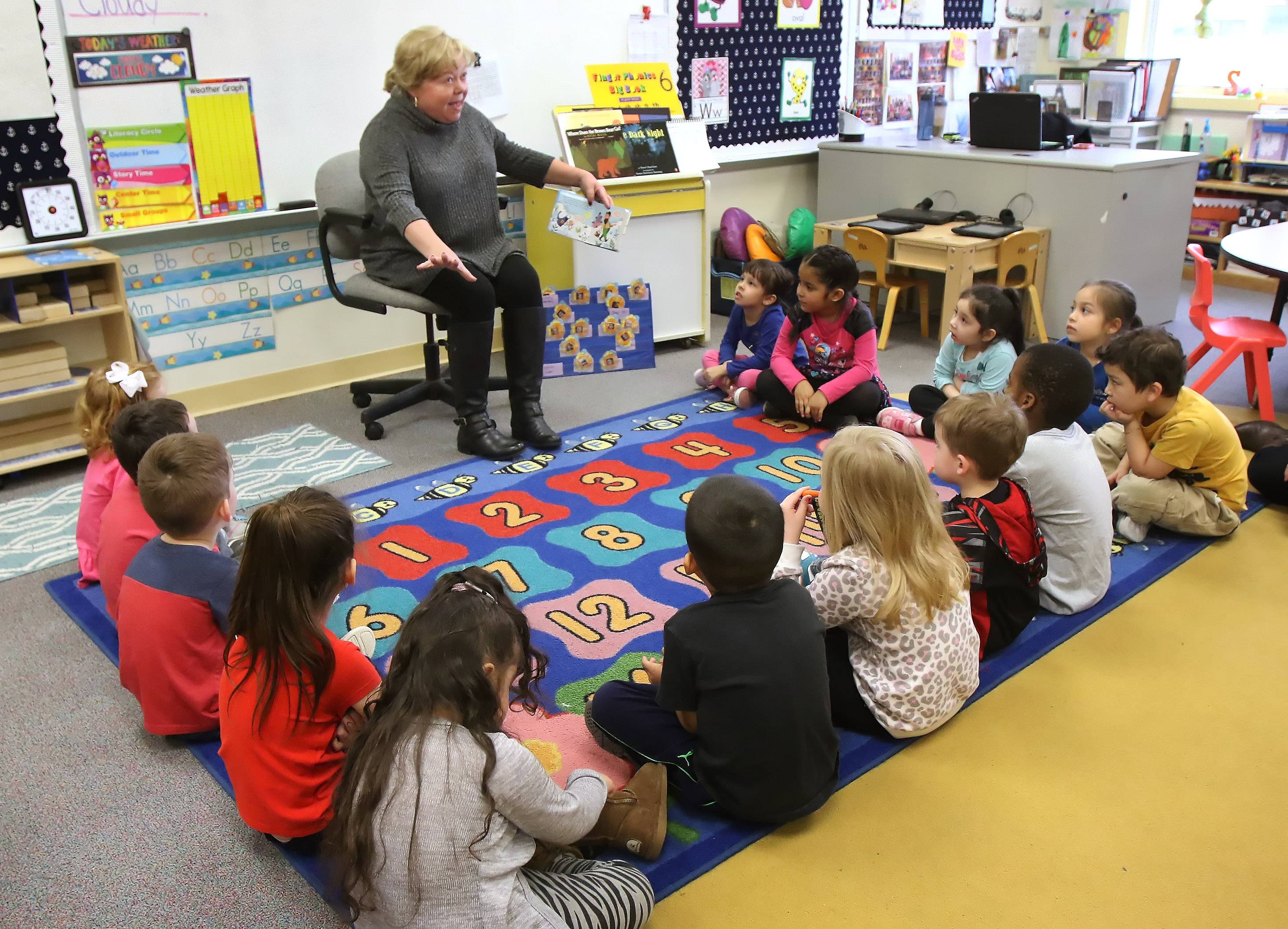 "Preschoolers listen as Ginny O'Connell, creative director at Cottage Door Press, reads ""Jack and the Beanstalk"" at the Round Lake Early Childhood Center on Tuesday. More than 50 books were donated by Cottage Door Press."