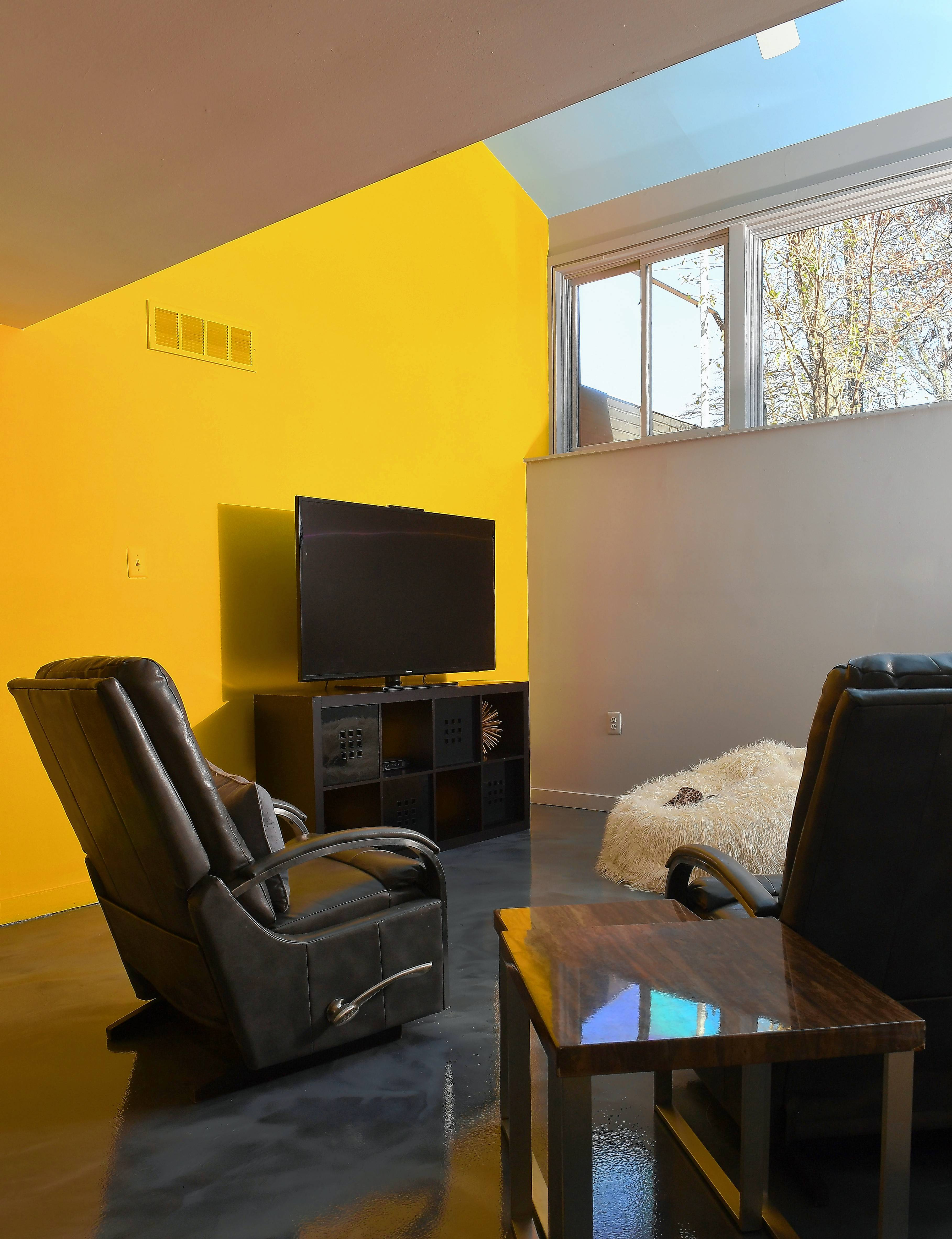 The Colemans' basement has a yellow accent wall, pale blue ceiling and gray walls.