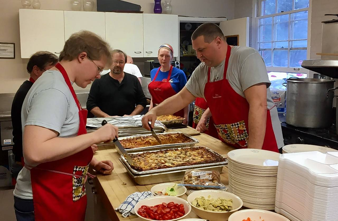 After a full day of cooking, volunteers prepare to serve lasagna during a recent free pasta dinner at St. Charles Episcopal Church.