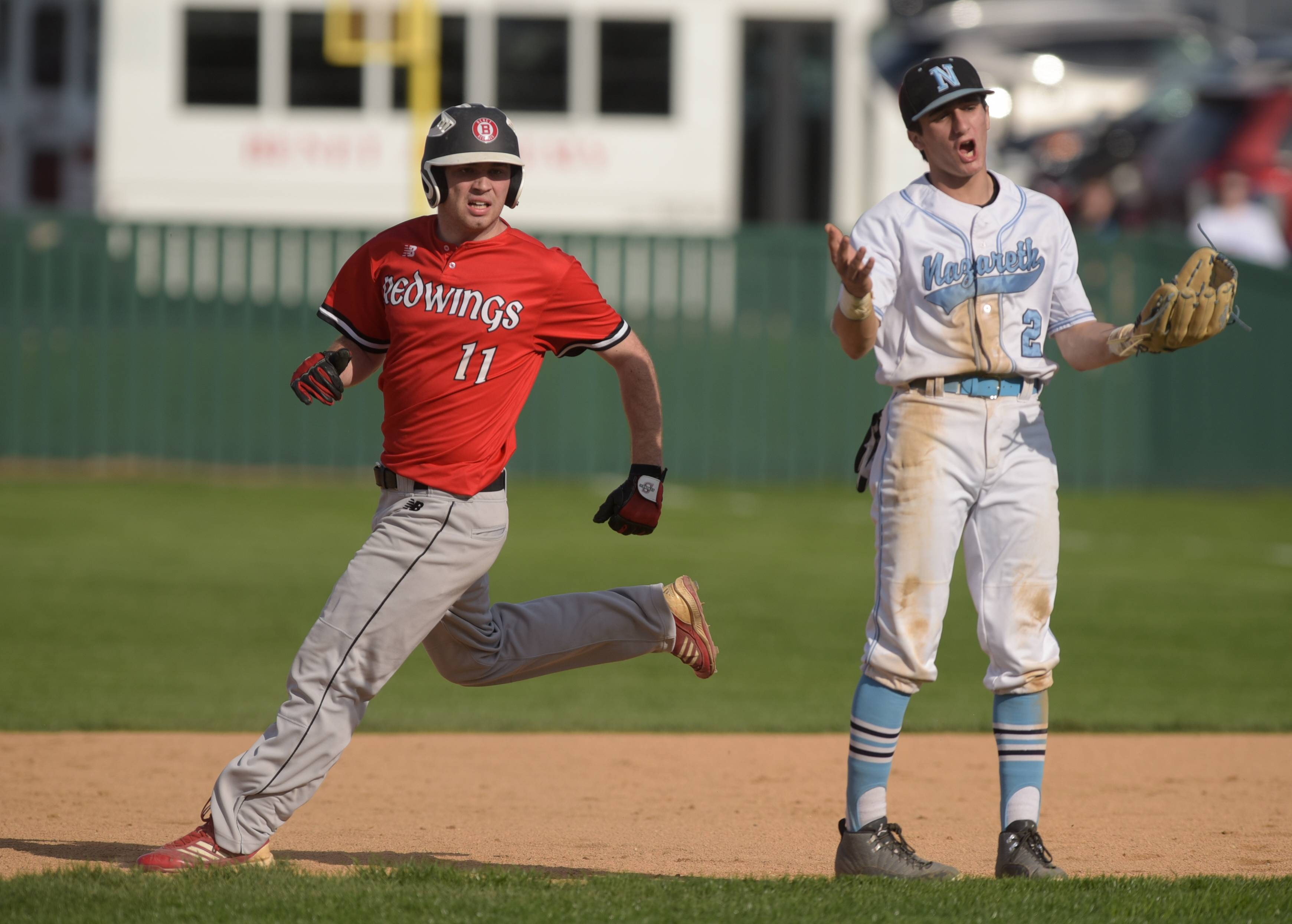 Benet Academy's Mike Dunn looks toward home plate as Nazareth's Dominic Milano reacts to a running scoring while  he was involved in a run down with Dunn between first and second, during varsity baseball in Lisle, April 18, 2017.