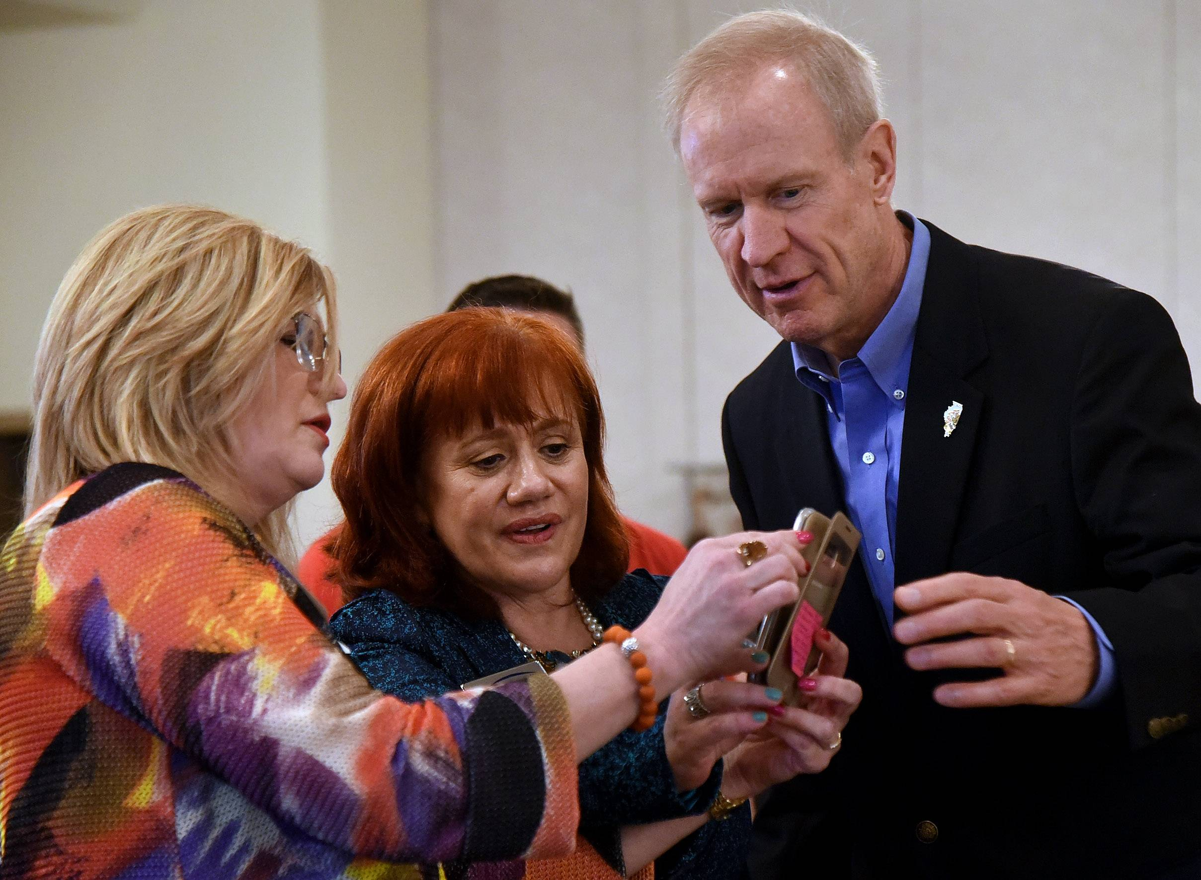 Kerry Jennejahn of Fifth Third Bank of Itasca, left, and Elizabeth Trezzi of the Bensenville Chamber of Commerce try for a selfie with Gov. Bruce Rauner, who spoke to the GOA Regional Business Association at a lunch Wednesday at Belvedere Banquets in Elk Grove Village.