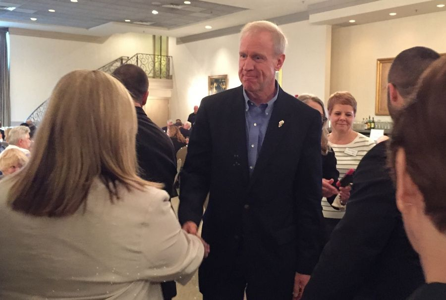 Gov. Bruce Rauner shakes hands with people attending a GOA Regional Business Association luncheon today in Elk Grove Village.
