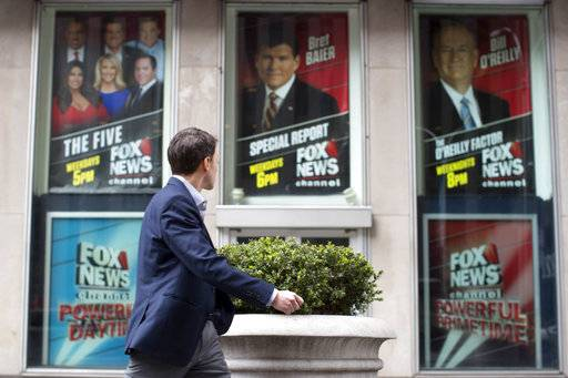 A pedestrian walks past the News Corp. headquarters building in New York displaying posters featuring Fox News Channel personalities including Bill O'Reilly, right, on Wednesday.