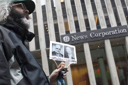 "Activist Judah Friedlander holds his ""Activist Barbie"" with a photo of Bill O'Reilly, right, next to politician Bull Connor, who strongly opposed activities of the American Civil Rights Movement in the 1960s, Wednesday in front of the News Corp. headquarters in Midtown Manhattan."