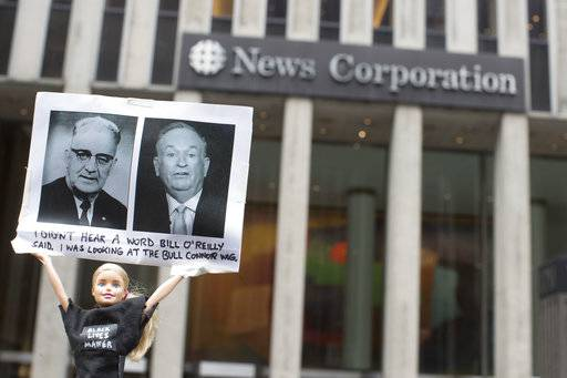 "Activist Judah Friedlander holds his ""Activist Barbie"" with a photo of Bill O'Reilly, right, next to politician Bull Connor, who strongly opposed activities of the American Civil Rights Movement in the 1960s, in front of the News Corp. headquarters in Midtown Manhattan, Wednesday, April 19, 2017. O'Reilly has lost his job at Fox News Channel after allegations that he sexually harassed women. (AP Photo/Mary Altaffer)The Associated Press"