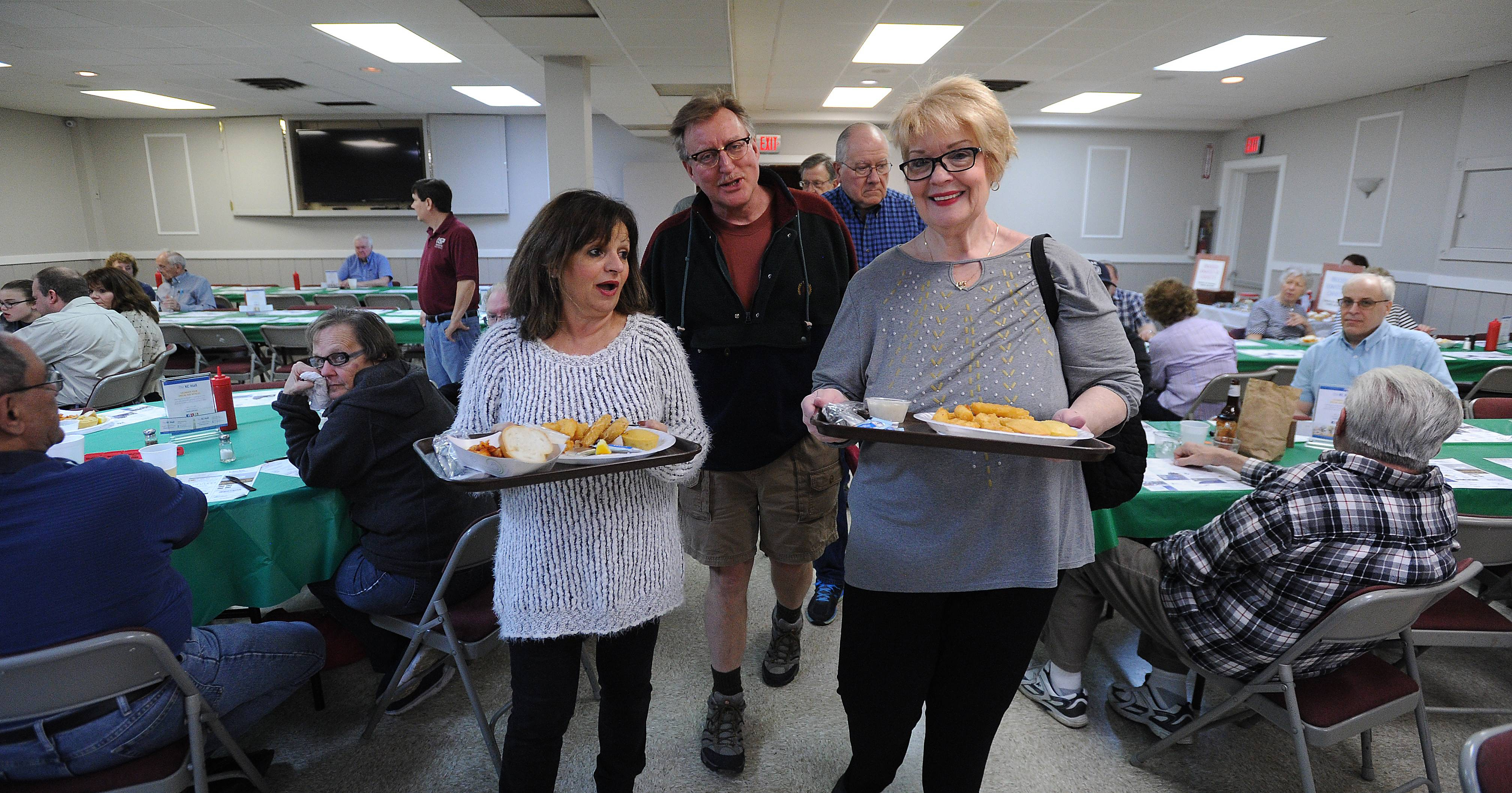 Mark Stastny, director of marketing at the Knights of Columbus Hall in Arlington Heights, talks with Mary Lee and Kathy Hoyos of Rolling Meadows during a recent Lenten fish fry in the renovated main hall.