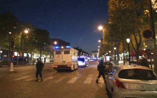 In this image made from video, police attend the scene after an incident on the Champs-Elysees in Paris, Thursday April 20, 2017.  French media are reporting that two police officers were shot Thursday on the famed shopping boulevard and the area has been evacuated.
