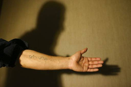 "In this March 21, 2017 photograph, Mohammmed, last name not given, shows a tattoo on his forearm that reads in Arabic: ""All for you, mother"", during an interview with The Associated Press, in Gaziantep, southeastern Turkey. He was barely 20 when Islamic State group militants stormed his home city of Deir el-Zour in the oil-rich east of Syria. Mohammed had already been fighting government forces the past two years, so it was an easy decision for him: Join the militants to keep up the battle against President Bashar Assad's rule."