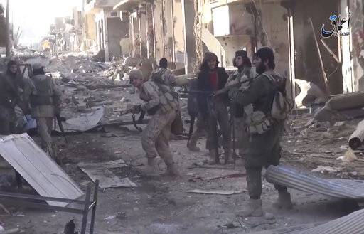 This image made from militant video posted online on Tuesday, December 24, 2015, by the Aamaq News Agency, a media arm of the Islamic State group, purports to shows Islamic State fighters fire during a a battle against the Syrian government forces, at al-Sinaa neighborhoods, in the oil-rich city of Deir el-Zour, east of Syria. (Aamaq News Agency, via AP)