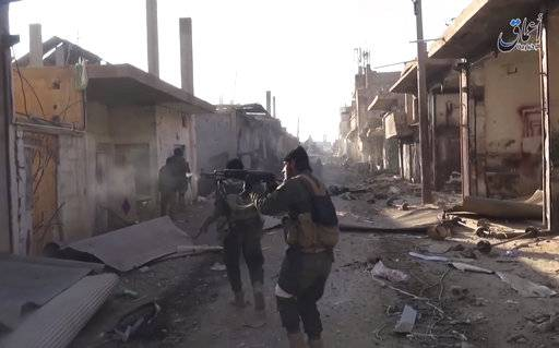 This image made from militant video posted online on Tuesday, December 24, 2015, by the Aamaq News Agency, a media arm of the Islamic State group, purports to shows Islamic State fighters fire during a a battle against the Syrian government forces, at al-Sinaa neighborhoods, in the oil-rich city of Deir el-Zour, east of Syria.(Aamaq News Agency, via AP)