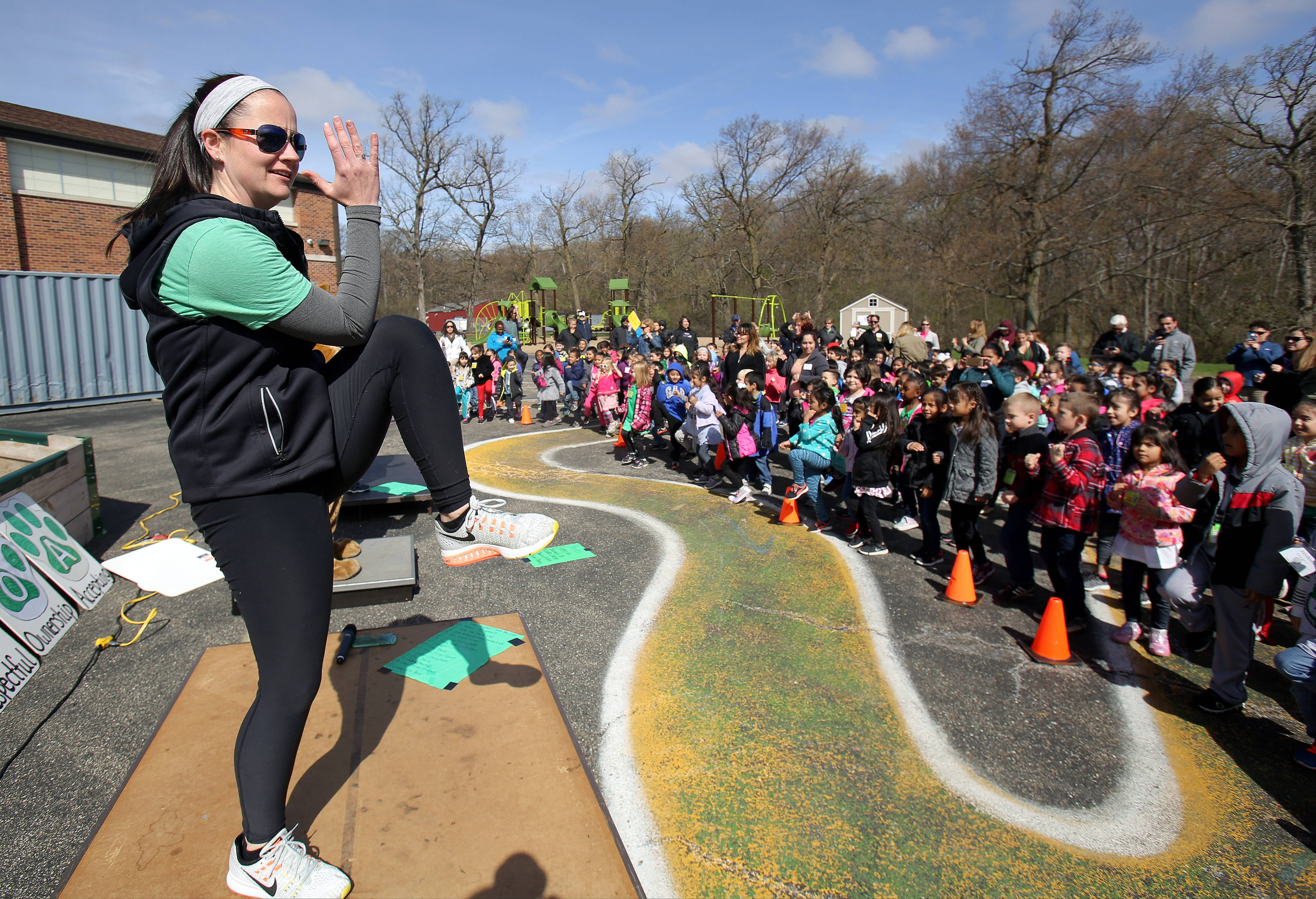 Physical education teacher Ashley Campbell leads Woodland Primary School kindergartners and their parents in a group exercise session Friday as students celebrated Earth Day in Gages Lake.