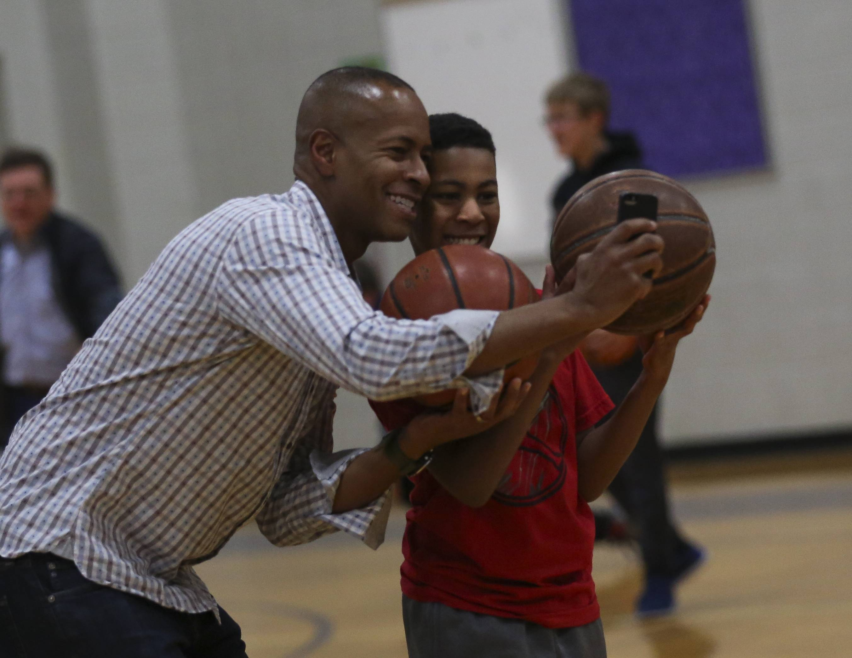 Mark Tucker and his sixth-grade son Jacob Porch-Tucker save a selfie while shooting hoops as part of the Books and Breakfast 4 Boys event at Crone Middle School in Naperville.