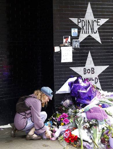 "FILE - In this April 22, 2016 file photo, a woman places flowers at a memorial at First Avenue in Minneapolis where pop super star Prince often performed. At his home and recording studio-turned-museum, a full four days of events are on tap for the one-year anniversary of his death on April 21, 2016, ranging from concert performances by the great one's former band mates to panel discussions on his legacy. Fans who can't afford those high-dollar tickets can head to a street party outside the club he made famous in ""Purple Rain."""