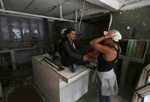 Butcher shop owner Liliana Altuna, left, speaks with an employee inside her shop that was looted the night before, at El Valle neighborhood in Caracas, Venezuela, Friday, April 21, 2017. At least 12 people were killed overnight following looting and violence in Venezuela's capital amid a spiraling political crisis, authorities said Friday. Most of the deaths took place in El Valle, a working class neighborhood near Caracas' biggest military base where opposition leaders say a group of people were hit with an electrical current while trying to loot a bakery protected by an electric fence. (AP Photo/Fernando Llano)