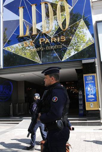 A riot police officer patrols outside the Lido cabaret on the Champs Elysees boulevard in Paris, Friday, April 21, 2017. France began picking itself up Friday from another deadly shooting claimed by the Islamic State group, with President Francois Hollande convening the government's security council and his would-be successors in the presidential election campaign treading carefully before voting this weekend.