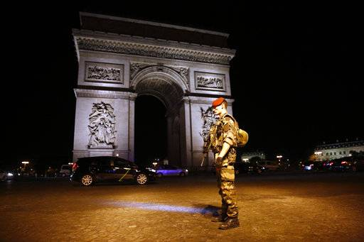 A soldier stands guard near the Arc of Thriomphe at the top of the Champs Elysees avenue in Paris, after a fatal shooting in which a police officer was killed along with an attacker, Thursday, April 20, 2017. French media are reporting that two police officers were shot Thursday on the famed shopping boulevard. Many police vehicles can be seen on the avenue that passes many of the city's most iconic landmarks.