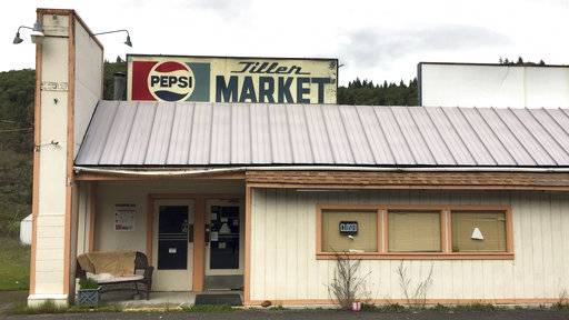 In this April 5, 2017 photo, the Tiller Market stands abandoned in downtown Tiller, Ore. Tiller, a dot on a map in remote southwestern Oregon, is for sale for $3.5 million, including the market, and the elementary school is for sale separately for $350,000. A potential buyer has come forward but is remaining anonymous -- and back-up offers are still being accepted. (AP Photo/Gillian Flaccus)