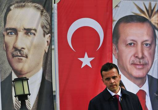 In this Monday, April 3, 2017 photo, a member of security for Erdogan stands guard following a speech at a rally in his hometown Black Sea city of Rize, Turkey, backdropped by banners showing modern Turkey's founder Mustafa Kemal Ataturk, left, and Turkey's current President Recep Tayyip Erdogan. The personality cult that grew around Ataturk has very gradually been fading as current President Recep Tayyip Erdogan, in power since 2003 as alternately prime minister and president, has harked back to the glory days of the height of the Ottoman Empire to whip up patriotic sentiment.