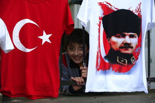 In this Tuesday, April 4, 2017 photo, a child from inside his schoolyard, peers out from behind a fence where t-shirts with the Turkish flag, and the picture of modern Turkey's founder Mustafa Kemal Ataturk, are offered for sale in the Black Sea city of Rize, Turkey. The eroding personality cult of Ataturk suffered its biggest blow yet when Turkey voted April 16 to expand the powers of the presidency, undercutting the parliamentary system that Ataturk imposed nearly a century ago.