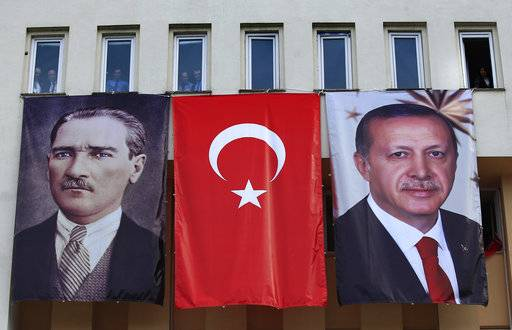 In this Monday, April 3, 2017 photo, banners showing modern Turkey's founder Mustafa Kemal Ataturk, left, and Turkey's current President Recep Tayyip Erdogan, right, decorate a building as people watch Erdogan's speech, during a rally for the upcoming referendum, in his hometown city of Rize, in the Black Sea region, Turkey. The personality cult that grew around Ataturk has very gradually been fading as current President Recep Tayyip Erdogan, in power since 2003 as alternately prime minister and president, has harked back to the glory days of the height of the Ottoman Empire to whip up patriotic sentiment.
