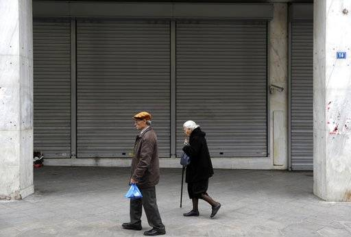 An elderly couple pass a closed bank in Athens, Friday, April 21, 2017. Greece's independent statistics agency says the country has posted a high primary budget surplus in 2016, at 3.9 percent of gross domestic product.