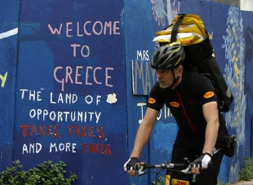 A courier with his bicycle passes graffiti on a wall in Athens, Friday, April 21, 2017. Greece's independent statistics agency says the country has posted a high primary budget surplus in 2016, at 3.9 percent of gross domestic product.