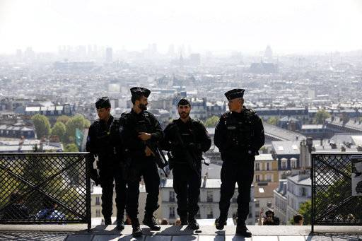 Riot police officers patrol in the Montmartre district Friday, April 21, 2017 in Paris. The shooting at the Champs Elysees rattled France only two days before the end of an unusually suspenseful election contest.