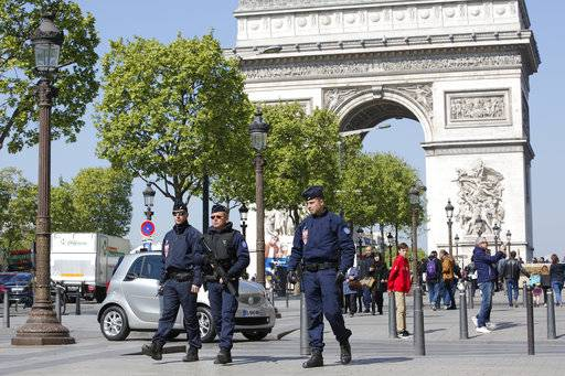 French riot police officers patrol on the Champs Elysees boulevard, with the Arc of Triomphe in background, in Paris, Friday, April 21, 2017. France began picking itself up Friday from another deadly shooting claimed by the Islamic State group, with President Francois Hollande convening the government's security council and his would-be successors in the presidential election campaign treading carefully before voting this weekend.