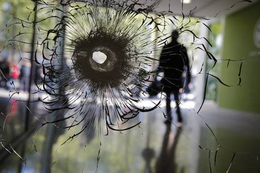 A bullet hole is pictured on a shopwindow of the Champs Elysees boulevard in Paris, Friday, April 21, 2017. France began picking itself up Friday from another deadly shooting claimed by the Islamic State group, with President Francois Hollande convening the government's security council and his would-be successors in the presidential election campaign treading carefully before voting this weekend. (AP Photo/Christophe Ena)
