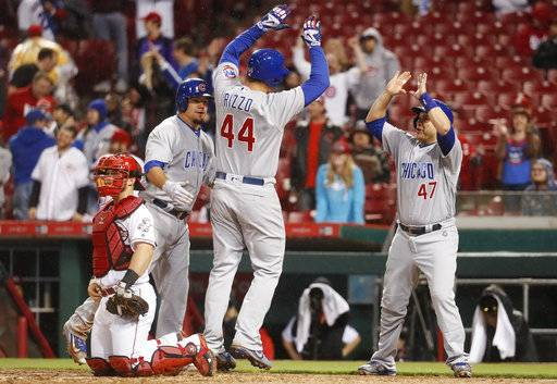 Chicago Cubs' Anthony Rizzo (44) celebrates his game-tying three-run home run with Kyle Schwarber, center left, and Miguel Montero (47) during the ninth inning of a baseball game, Friday, April 21, 2017, in Cincinnati. The Cubs defeated the Cincinnati Reds 6-5. (AP Photo/John Minchillo)