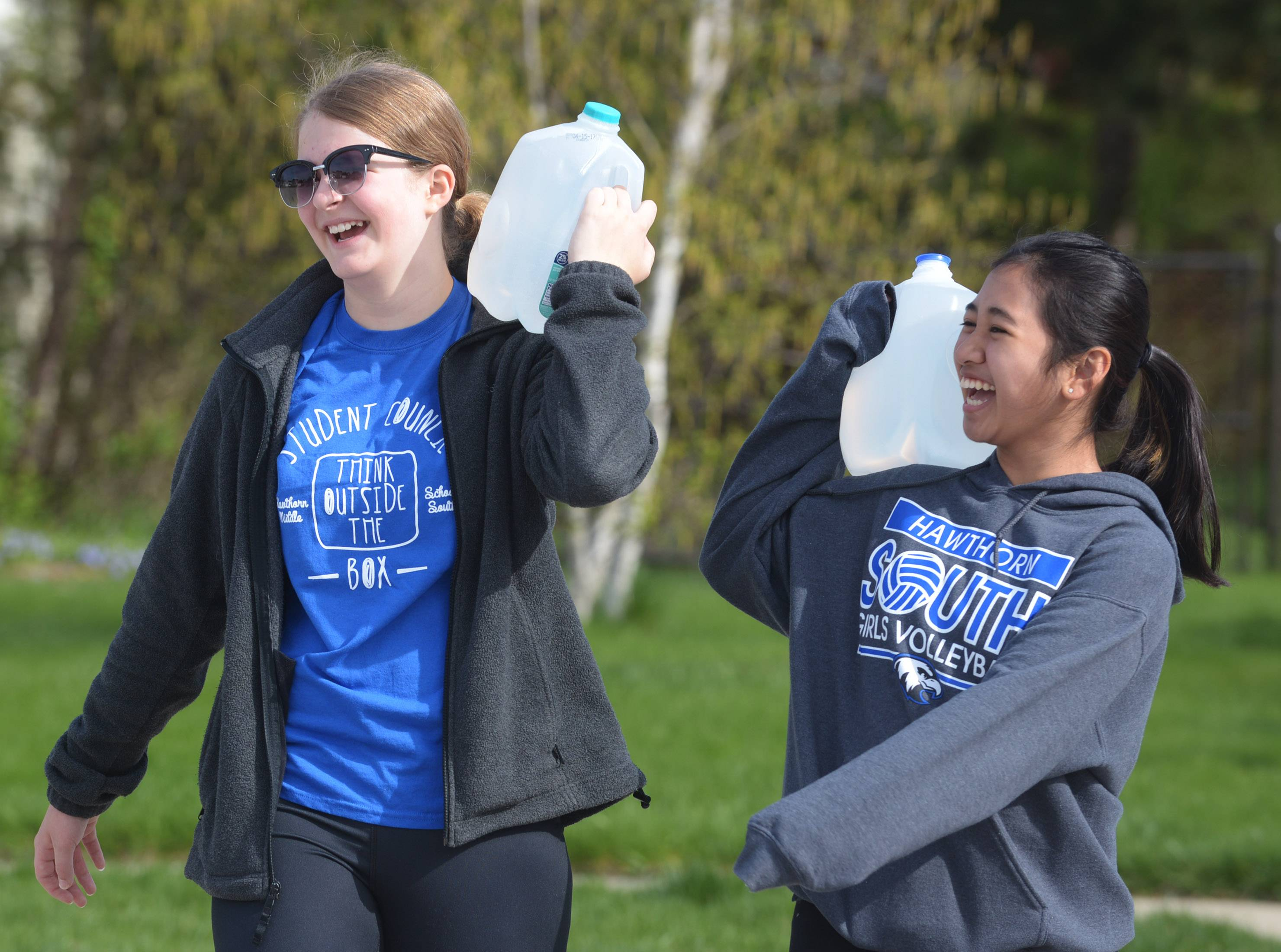 Allison Klemstein, left, and Sofia Sanchez are among a group of students from Hawthorn Middle School South in Vernon Hills re-enacting what it's like for women and children in other parts of the world to carry jugs of water great distances because they do not have access water near their homes and villages.