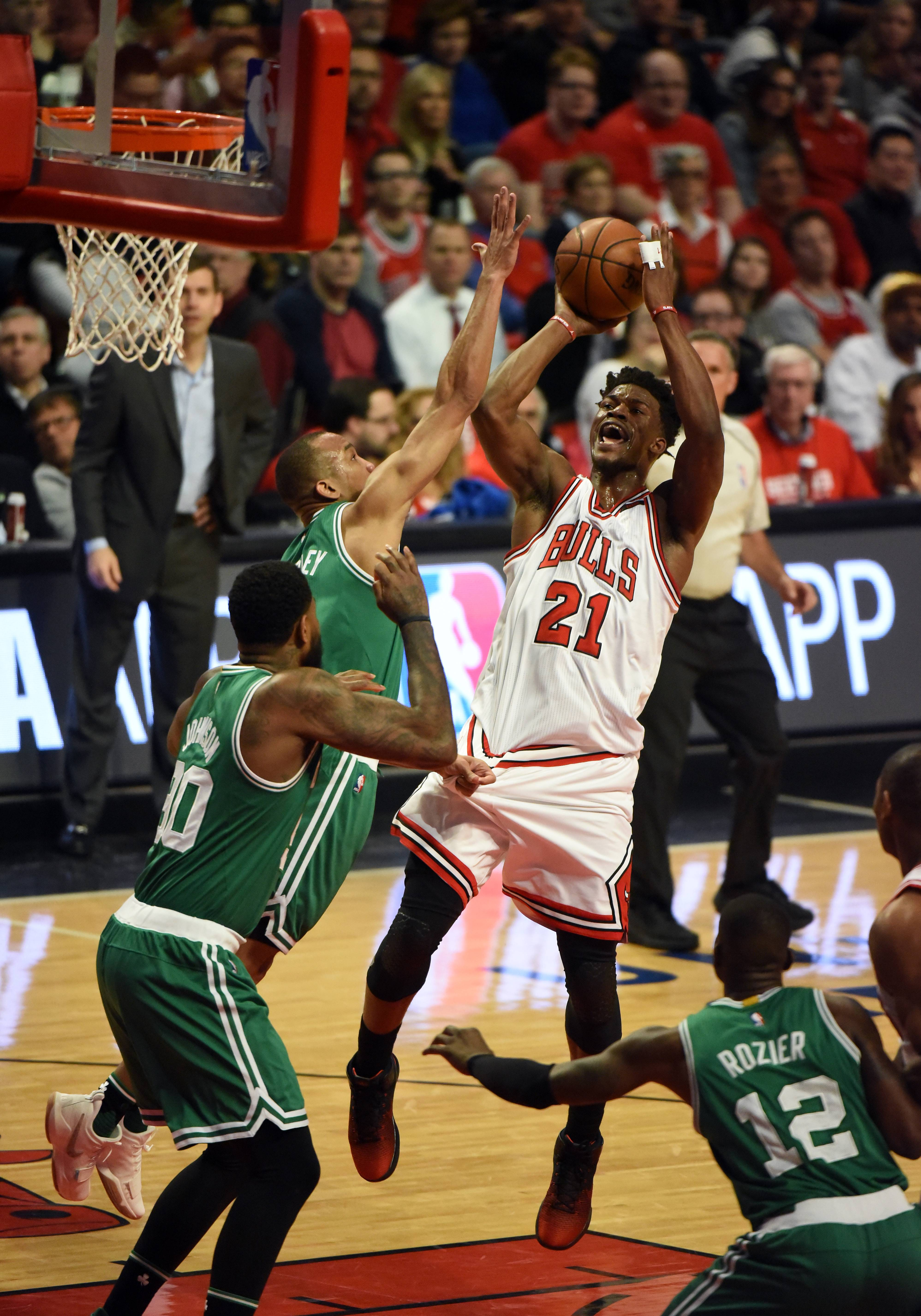 Chicago Bulls' Jimmy Butler, center, drives to the basket past Boston Celtics' Avery Bradley, left, and Al Horford during the first quarter of a first-round NBA playoff basketball game in Chicago, Friday, April 21, 2017. (AP Photo/Charles Rex Arbogast)
