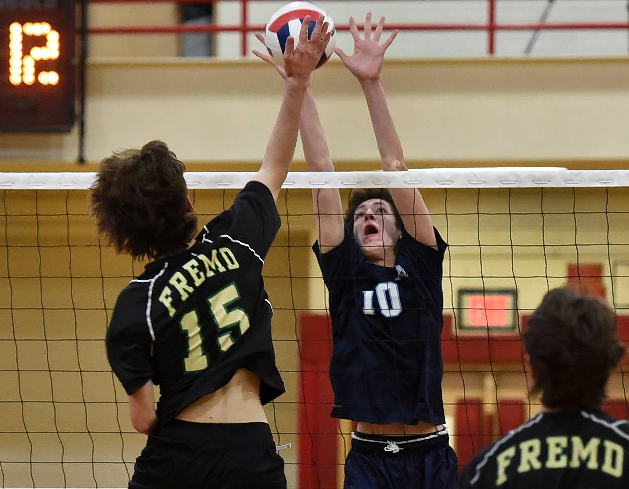 Prospect's Glenn Wiley goes up for a block on Fremd's Rocco Stella during the boys volleyball tournament at Schaumburg.