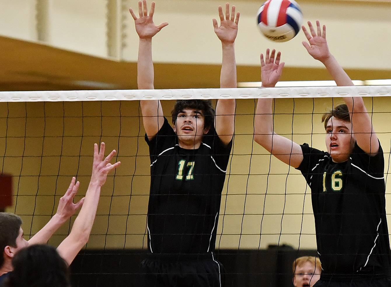 Fremd's Tanner Yates, left, and Ben Cohen try for a block against Prospect's Connor Riordan during the boys volleyball tournament at Schaumburg.