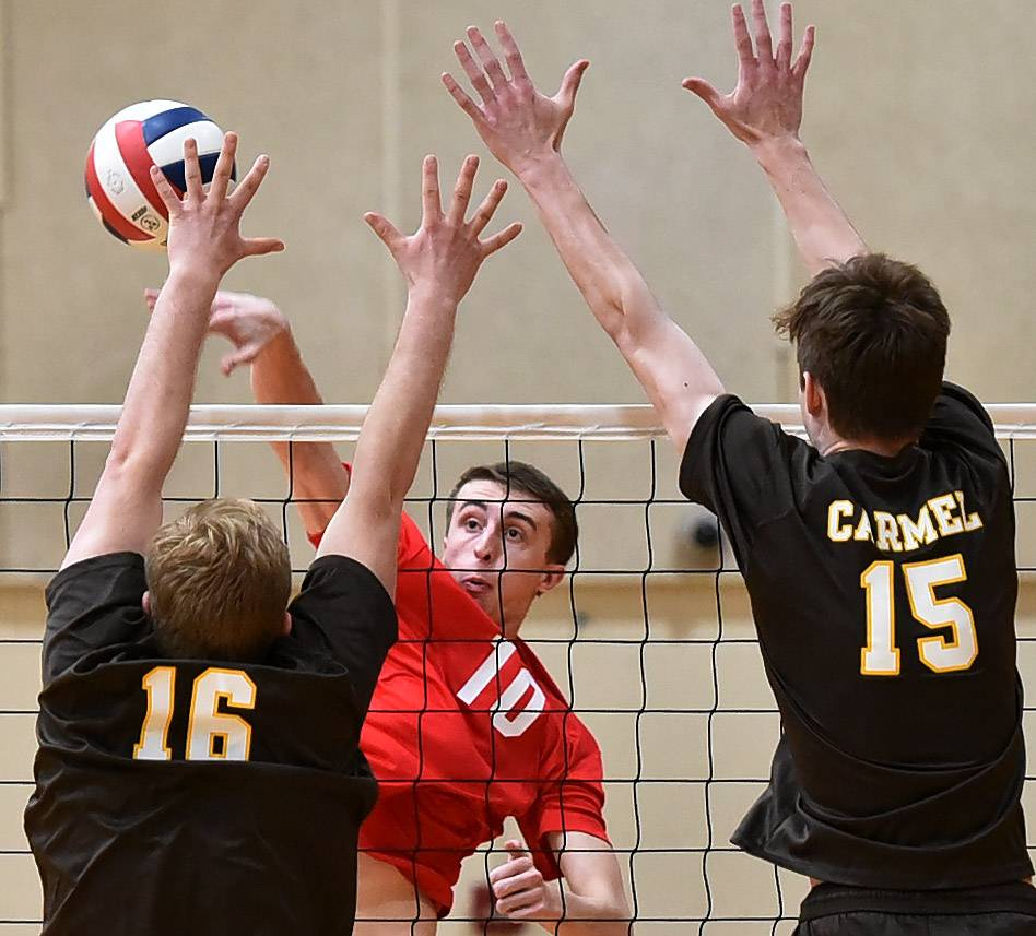Huntley's Luke Mahnke spikes past Carmel's Maksym Kolomayets, left and Mike Scott during the boys volleyball tournament at Schaumburg High School.