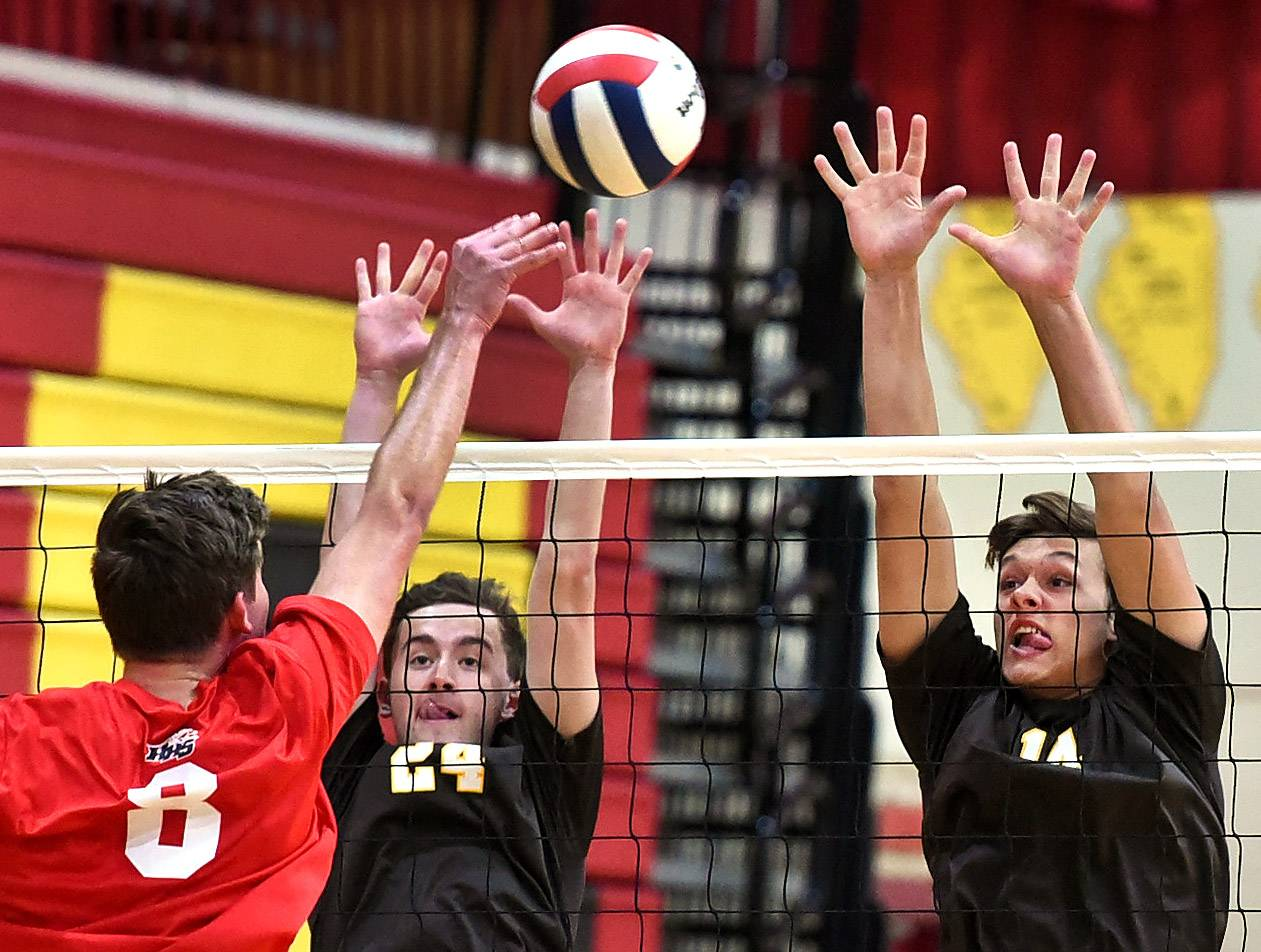 Carmel's Ben Burkhalter, left, and Jimmy Harvey try to block a shot by Huntley's John Galason, during the boys volleyball tournament at Schaumburg High School.