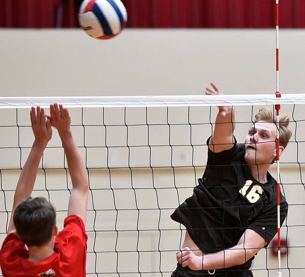 Maksym Kolomayets of Carmel spikes a ball past Huntley's Nick Brimie, during the boys volleyball tournament at Schaumburg High School.