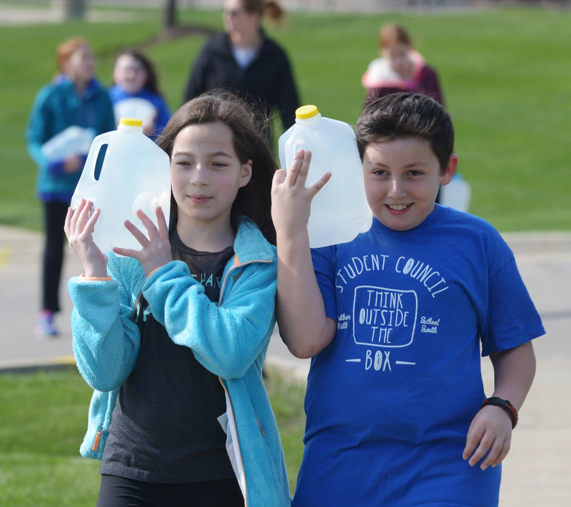 Lia Alterson, left, and Dylan Tehrani are sixth graders from Hawthorn Middle School South in Vernon Hills re-enacting what it's like for women and children in other parts of the world to carry jugs of water great distances because they do not have access water near their homes and villages.
