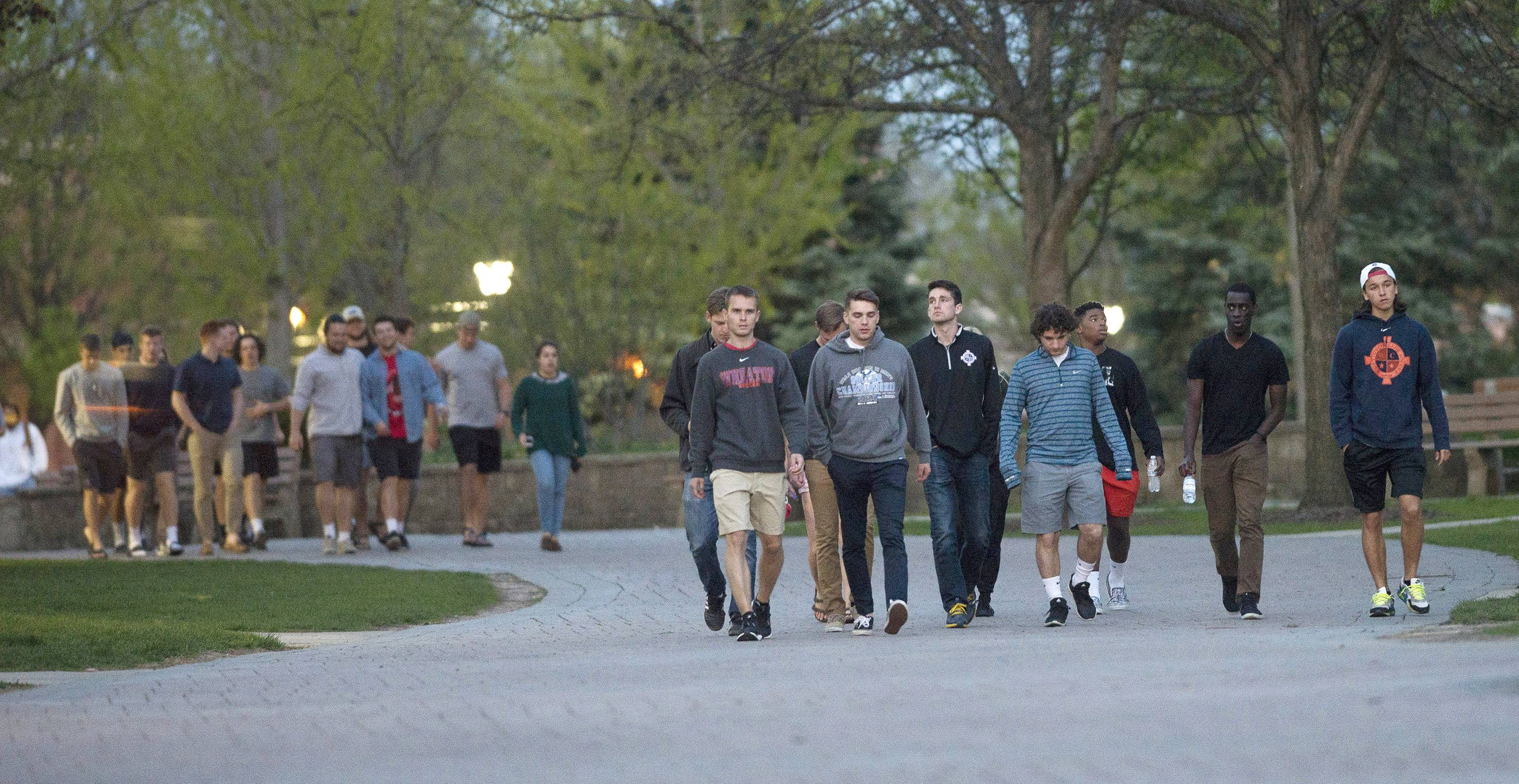 Groups of students walk on the Wheaton College campus Sunday for a worship service at Pierce Memorial Chapel in memory of freshman Ethan Roser of Cincinnati. Roser died Saturday after an accident at a track meet.