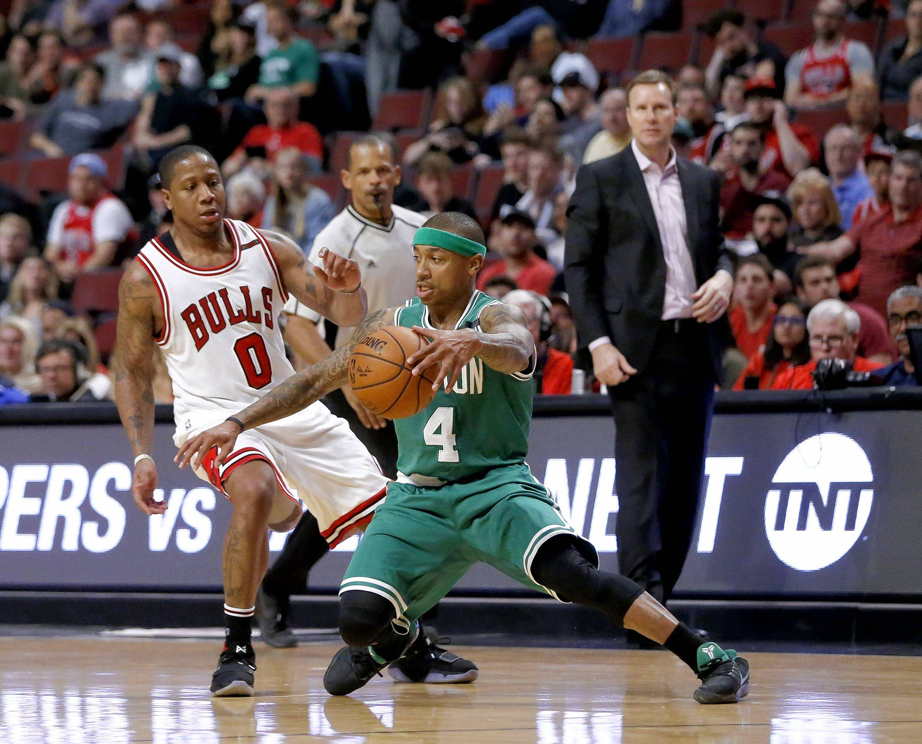 Boston Celtics' Isaiah Thomas (4) controls the ball from Chicago Bulls' Isaiah Canaan (0) as head coach Fred Hoiberg watches during the second half in Game 4 of an NBA basketball first-round playoff series in Chicago, Sunday.